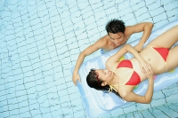 Couple in swimming pool, woman lying on pool raft, man next to her - Asia Images Group