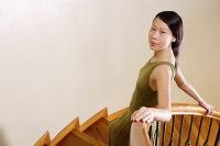 Woman leaning on staircase, looking at camera - Asia Images Group