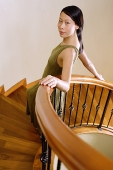 Woman leaning on staircase, looking at camera, portrait - Asia Images Group