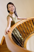 Woman standing on staircase, looking at camera - Asia Images Group