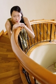 Woman on staircase, leaning on banister, looking at camera - Asia Images Group