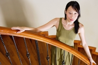 Woman standing on staircase, hands on banister - Asia Images Group
