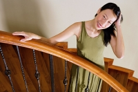 Woman standing on staircase, hand on head, smiling - Asia Images Group