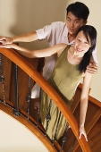 Couple standing on staircase, smiling at camera - Asia Images Group