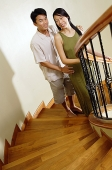 Couple on staircase, smiling at camera - Asia Images Group