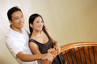 Couple standing at staircase, smiling - Asia Images Group