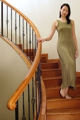 Woman walking on staircase, looking at camera - Asia Images Group