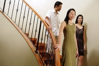 Young adults walking down stairs, smiling - Asia Images Group