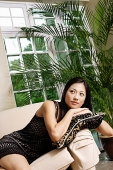 Woman lying on arm chair, leaning on cushion, looking away - Asia Images Group
