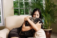 Woman on arm chair, hugging cushion - Asia Images Group