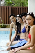 Young adult couples sitting at edge of swimming pool - Asia Images Group