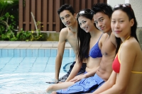 Young adult couples sitting at edge of swimming pool, side view - Asia Images Group