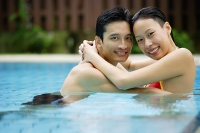 Couple in swimming pool, embracing, smiling at camera - Asia Images Group