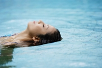 Woman floating in swimming pool - Asia Images Group