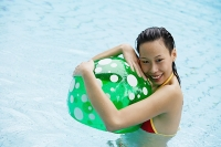 Woman in swimming pool, hugging beach ball, smiling - Asia Images Group