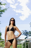 Woman in bikini and sunglasses, hand on hip - Asia Images Group