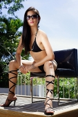 Woman in bikini, wearing high heels, sitting on chair,  facing camera - Asia Images Group
