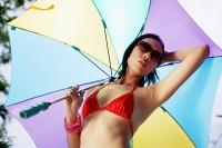 Woman in bikini and sunglasses, holding umbrella - Asia Images Group