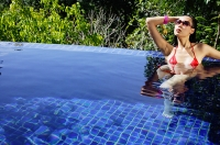 Woman in red bikini, sitting in swimming pool, hand on head - Asia Images Group