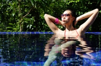 Woman sitting in swimming pool, sunbathing - Asia Images Group
