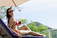 Young woman in bikini, lying on deck chair, holding drink, turning to look over shoulder - Asia Images Group