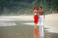 Couple walking along beach, holding hands - Asia Images Group