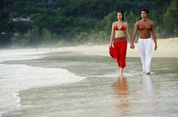 Couple walking side by side along beach, holding hands - Asia Images Group