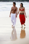 Couple walking side by side along beach, holding hands, looking away - Asia Images Group