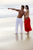 Couple standing on beach, holding hands, man pointing - Asia Images Group