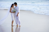 Bride and groom on beach, standing face to face - Asia Images Group