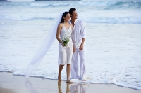 Bride and groom walking on beach - Asia Images Group