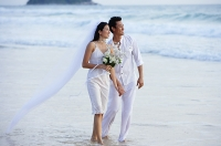 Bride and groom walking on beach, holding hands, looking away - Asia Images Group