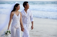 Newlyweds walking on beach, holding hands, looking away - Asia Images Group