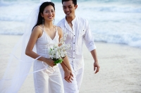 Newlyweds walking on beach, smiling - Asia Images Group