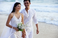 Bride and groom walking on beach, smiling - Asia Images Group