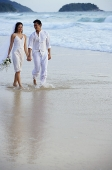 Bride and groom walking on beach, holding hands - Asia Images Group