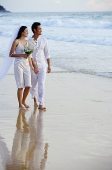 Bride and groom walking on beach, looking out to sea - Asia Images Group