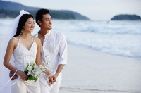 Bride and groom standing on beach, holding hands, looking away - Asia Images Group