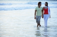 Couple walking on beach, ankle deep in water, holding hands - Asia Images Group