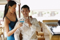 Couple toasting with drinks, man looking at camera - Asia Images Group