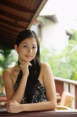 Woman wearing halter top, hand on chin, looking at camera - Asia Images Group