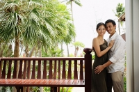 Couple standing cheek to cheek, embracing, smiling - Asia Images Group