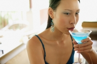 Woman sipping cocktail - Asia Images Group