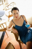 Woman sitting on bar stool, holding drink, looking at camera - Asia Images Group