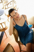 Woman sitting on bar stool, holding drink, smiling at camera - Asia Images Group