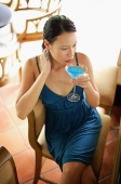 Woman sitting on chair, sipping cocktail, high angle view - Asia Images Group