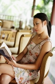 Woman sitting, reading a book - Asia Images Group