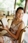Woman sitting, holding a book, looking over shoulder - Asia Images Group