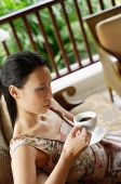 Woman sitting, holding cup and saucer - Asia Images Group