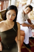 Woman standing, looking away, man sitting behind her - Asia Images Group
